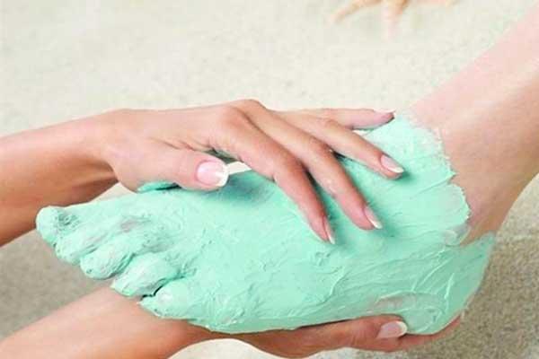 женские руки наносят масочку зелёного цвета на ножки