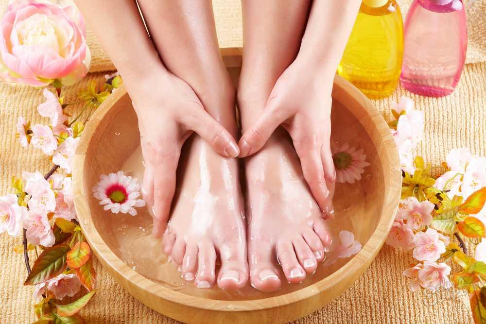 девушка держит ножки в ванночке с цветами