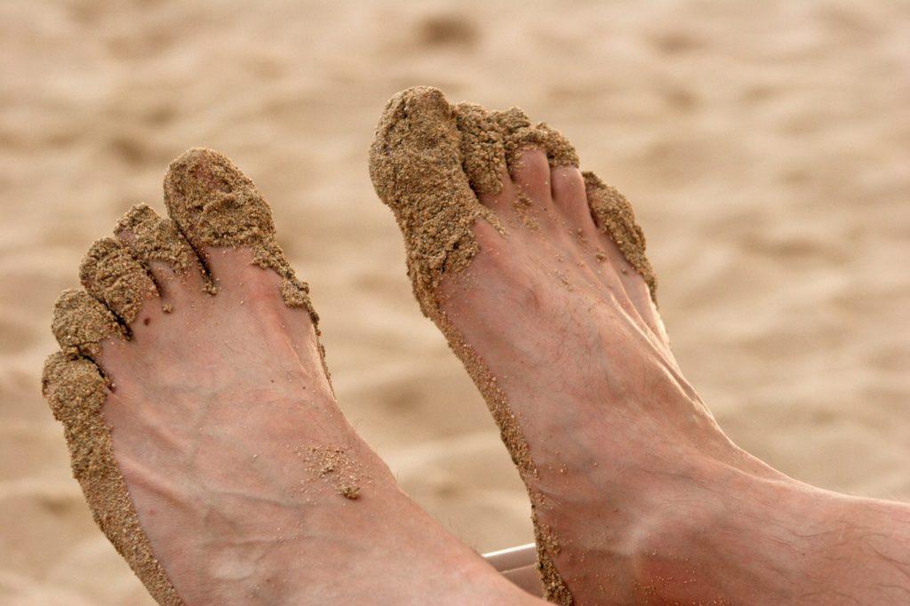 мужские стопы и ногти в песке