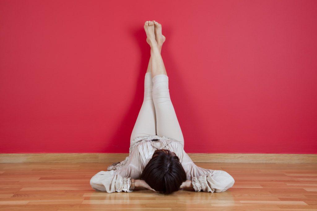 девушка лежит у стены с поднятыми вверх ногами и подложив под голову руки